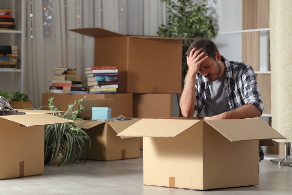 Sad evicted man moving home complaining on the floor, apartment moving
